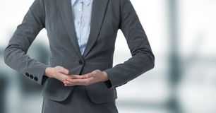 Business woman mid section with hands together in blurry grey office Stock Photos
