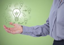 Business woman mid section with lightbulb doodles and flare in hand against green background Stock Photography