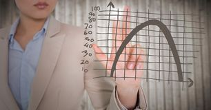Business woman mid section touching brown graph with flare against blurry wood panel Royalty Free Stock Photography