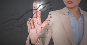 Business woman mid section touching grey graph with flare against grey background Stock Images