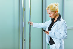 Business woman with mobile entering office Stock Images