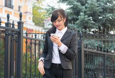 Business-woman with mobile phone on city street. Writes sms Royalty Free Stock Photography