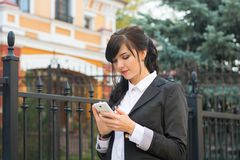 Business-woman with mobile phone on city street. Writes sms Royalty Free Stock Photo