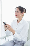 Business woman with mobile phone looking away Royalty Free Stock Photos