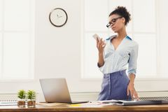 Business woman with mobile phone at office. Communication, technology, success. African-american business woman using mobile phone, standing at her workplace in Royalty Free Stock Image