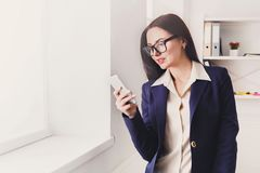 Business woman with mobile phone at office window. Communication, technology, success. Business woman using mobile phone near window at office workplace, copy Royalty Free Stock Photos