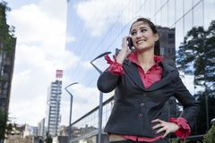 Business woman with a mobile phone on street Royalty Free Stock Images