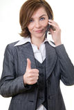 Business woman with mobile phone and thumb up. Picture of a business woman with mobile phone and her thumb up Stock Images