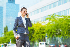 Business woman in modern office district talking cellphone Royalty Free Stock Photo