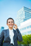 Business woman in modern office district talking cellphone Stock Images