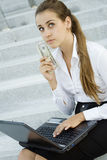 Business woman with money and a laptop Stock Photo