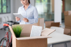 Business woman moving in a new office. She is using a digital tablet, selective focus, open cardboard box on foreground royalty free stock images
