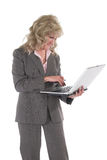 Business Woman Multitasking With Cellphone and Laptop 2. Attractive executive business woman standing up holding a laptop computer and cell phone Stock Photo