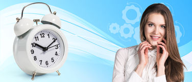 Business woman near classical alarm clock. On the blue abstract background stock photos