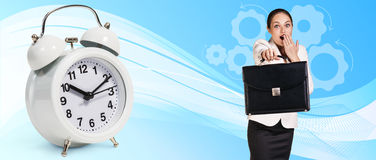 Business woman near classical alarm clock. On the blue abstract background royalty free stock photography