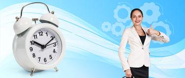 Business woman near classical alarm clock. On the blue abstract background royalty free stock photos