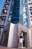 Business woman near contemporary building. Beautiful young business woman with long legs wearing white skirt and black blouse and standingg near hi tech Royalty Free Stock Images