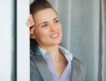 Business woman near window looking into distance Stock Images