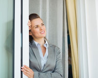 Business woman near window looking into distance Royalty Free Stock Image