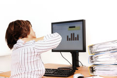 Business woman with neck pain. Sits on workplace with documents and monitor on table Royalty Free Stock Photo