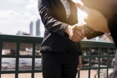 Business woman negotiate and shake hands with partner or investo. R outdoor on bridge, successful conversation and agreement concept royalty free stock image