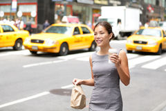 Business woman in New York City candid and real. Businesswoman in Manhattan walking in dress suit holding doggy bag drinking coffee smiling happy. Young royalty free stock photos