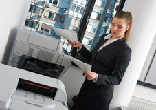 Business woman next to office printer. Business woman with documents standing next to printer Royalty Free Stock Images