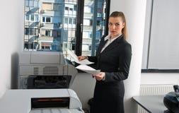 Business woman next to office printer Stock Photos
