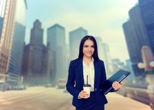Business woman with notebook and coffee in hands. Skyscrapers on background. Modern building, financial center, cityscape. Female businessperson in suit Royalty Free Stock Photos