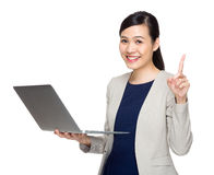 Business woman with notebook computer and finger point up Stock Photo