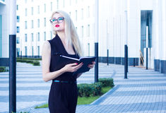 Business woman with a notebook looking into the distance on the background of the business center Royalty Free Stock Photos