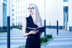 Business woman with a notebook looking into the distance on the background of the business center Royalty Free Stock Images