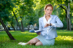 Business woman with notebook looking on her clock Royalty Free Stock Photos