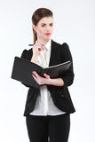 Business woman with a notebook and pen. Elegant businesswoman in black suit Royalty Free Stock Photos