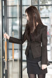Business woman with a notepad enters door Royalty Free Stock Photography