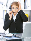 Business Woman in Office. Confused business woman working in office, wearing headset Royalty Free Stock Photography
