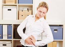 Business woman in office with back pain. Standing and holding her hip Stock Photography