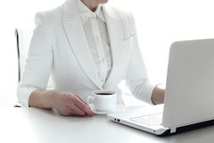 Business woman working with laptop and drinking coffee. Closeup of woman at office table   in white suit with laptop  working, typing  and drinking coffee Stock Photography
