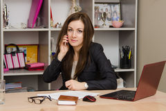Business woman at the office conducts a dialogue by phone Stock Image