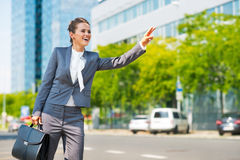 Business woman in office district catching taxi Royalty Free Stock Photography