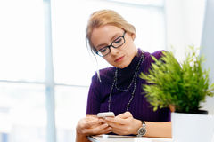 Business woman in office holding mobile phone Stock Images