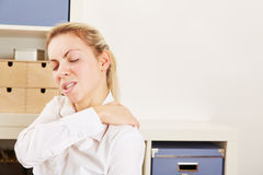 Business woman in office with pain in her shoulder Stock Photos