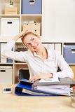Business woman in office stretching her nape. Young business woman in office stretching her tense nape with her hand Stock Photography