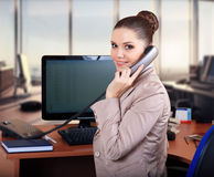 Business woman in the office talking on the phone. Woman On Phone In Busy Modern Office Stock Photos