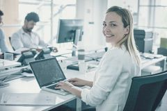 Woman using laptop and looking at camera. Colleagues working to stock photo
