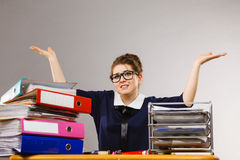 Business woman in office working gesturing. Sleepy business woman doing her work sitting working at desk full off documents in binders, gesturing empty hands Royalty Free Stock Images
