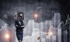 Business woman with old TV instead of head. Business woman in suit with old TV instead of head keeping arms crossed while standing against flying bulbs and Royalty Free Stock Images