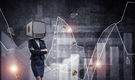 Business woman with old TV instead of head. Business woman in suit with old TV instead of head keeping arms crossed while standing against flying bulbs and Stock Images