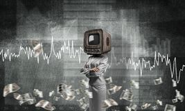 Business woman with old TV instead of head. Business woman in suit with old TV instead of head keeping arms crossed while standing against flying dollar Royalty Free Stock Images