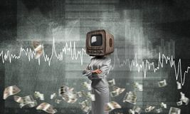 Business woman with old TV instead of head. Business woman in suit with old TV instead of head keeping arms crossed while standing against flying dollar Stock Image